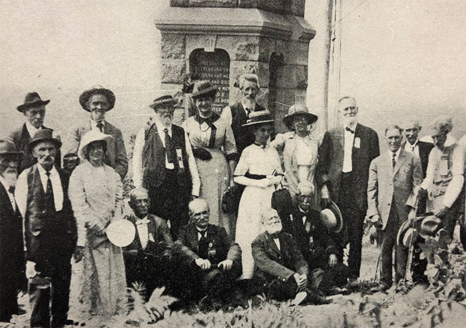 A crowd of people pose for a picture in front of the 91st Pennsylvania monument on the summit of Little Round Top.