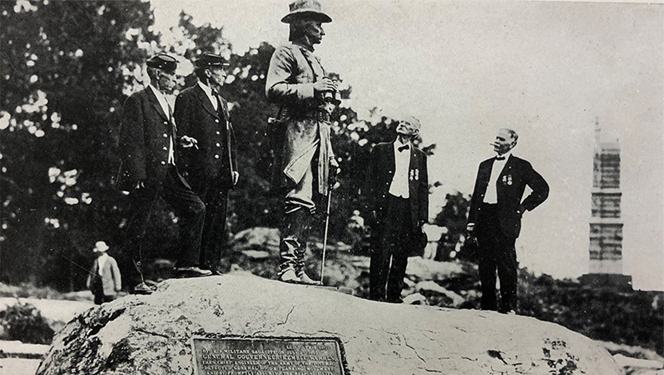 A group of Civil War veterans visit the statue to General Gouverneur Kemble Warren at the summit of Little Round Top.