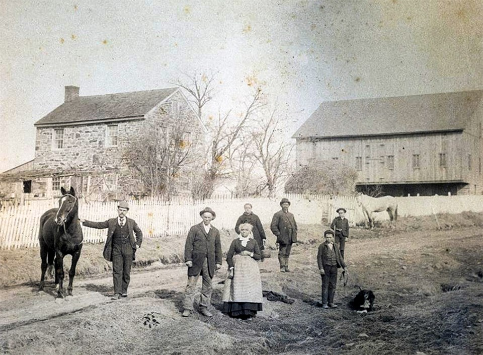 A black and white picture of a large african american family, a horse, a dog, and a house and barn.