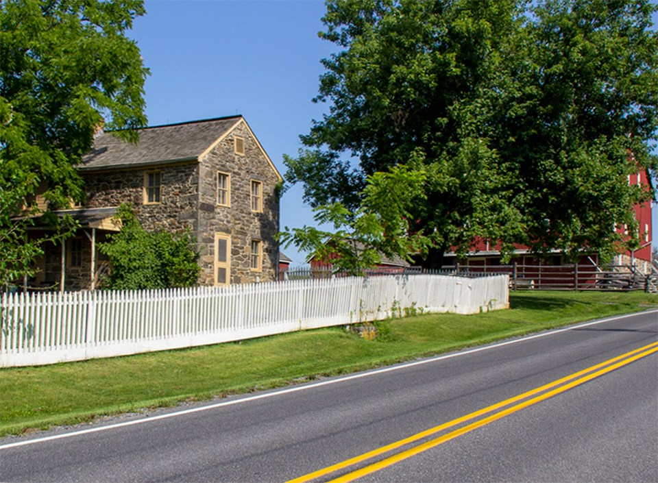 A stone house with white picket fence stands alongside a road.