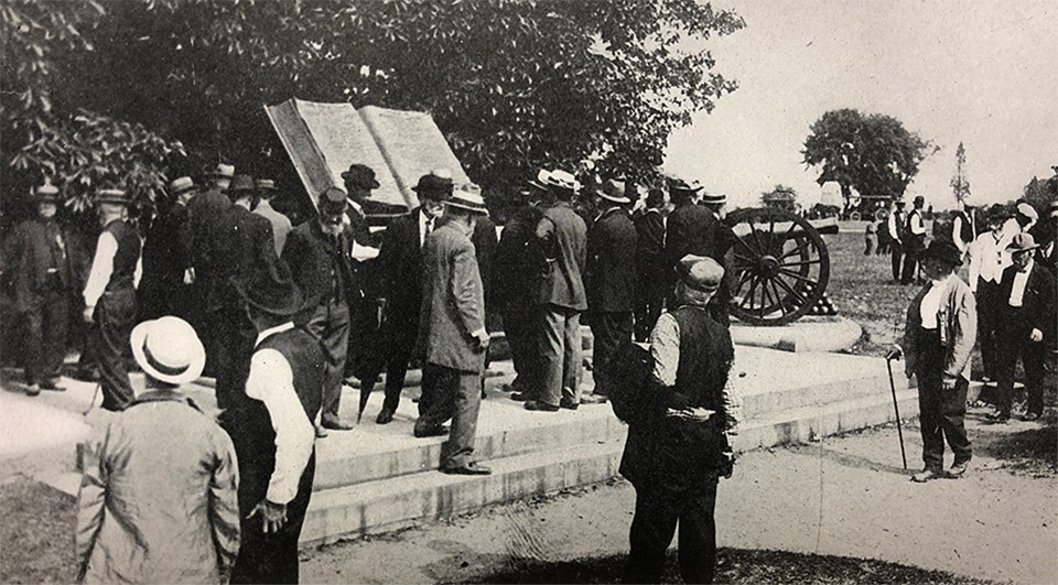 Civil War veterans gather around a large book shaped monument next to a grove of trees.