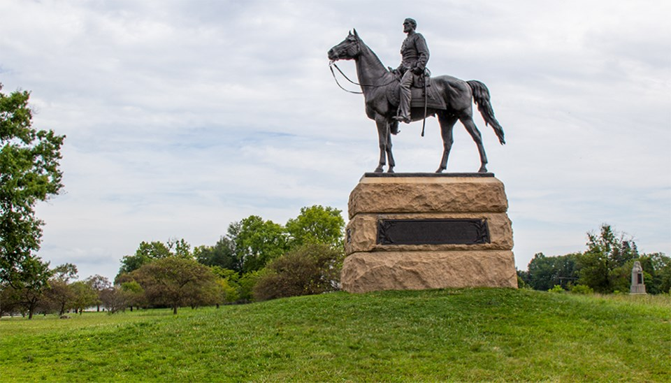 A large equestrian statue stands on a grass lawn in front of a grove of trees.