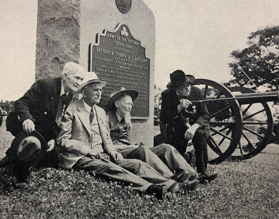 Four Civil War veterans sit at the base of a small monument as one of them points with his cane. A cannon sits in the background.