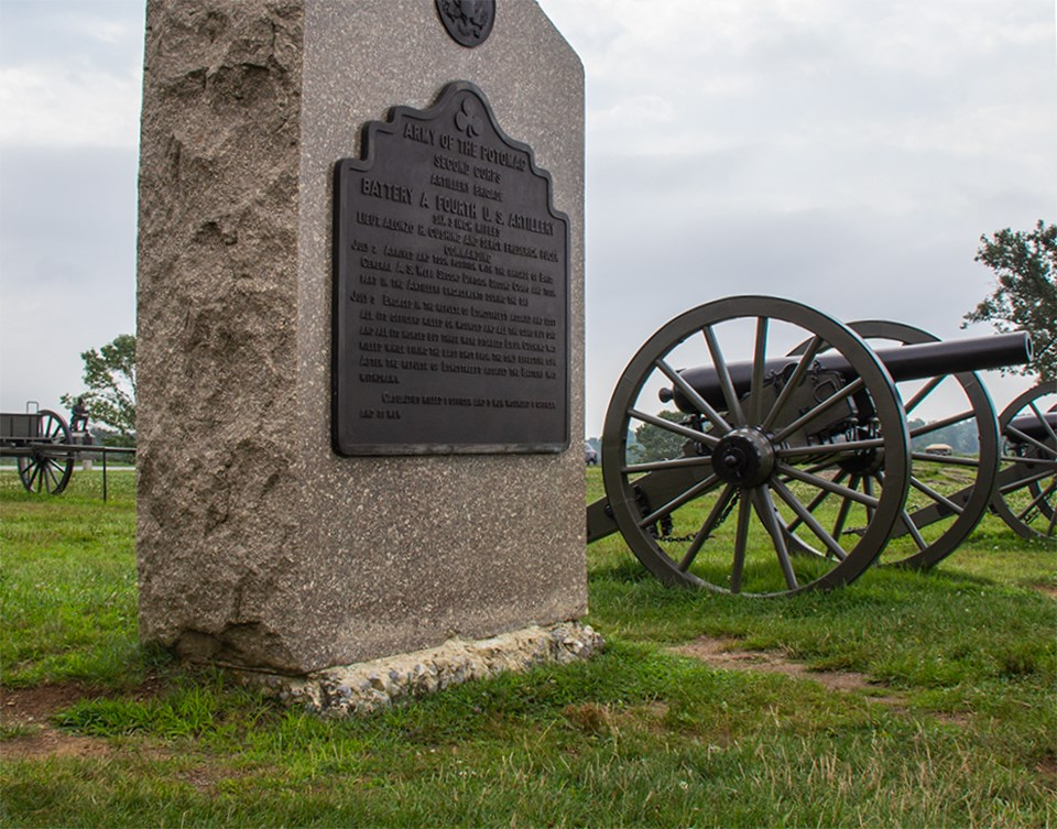 A small monument and cannon sit close to each other.