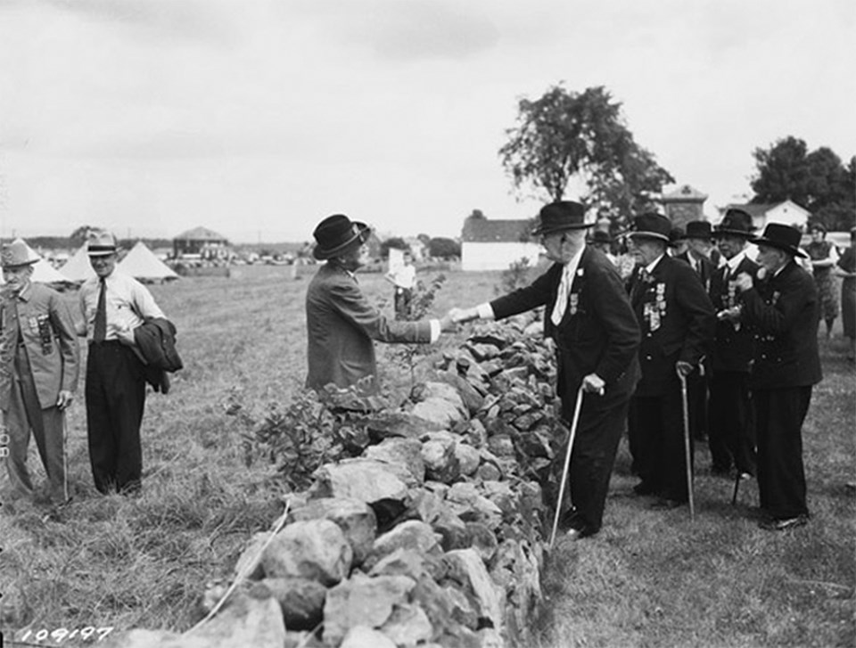 A Confederate veteran and a Union veteran shake hands over a stone wall. Other veterans watch on.