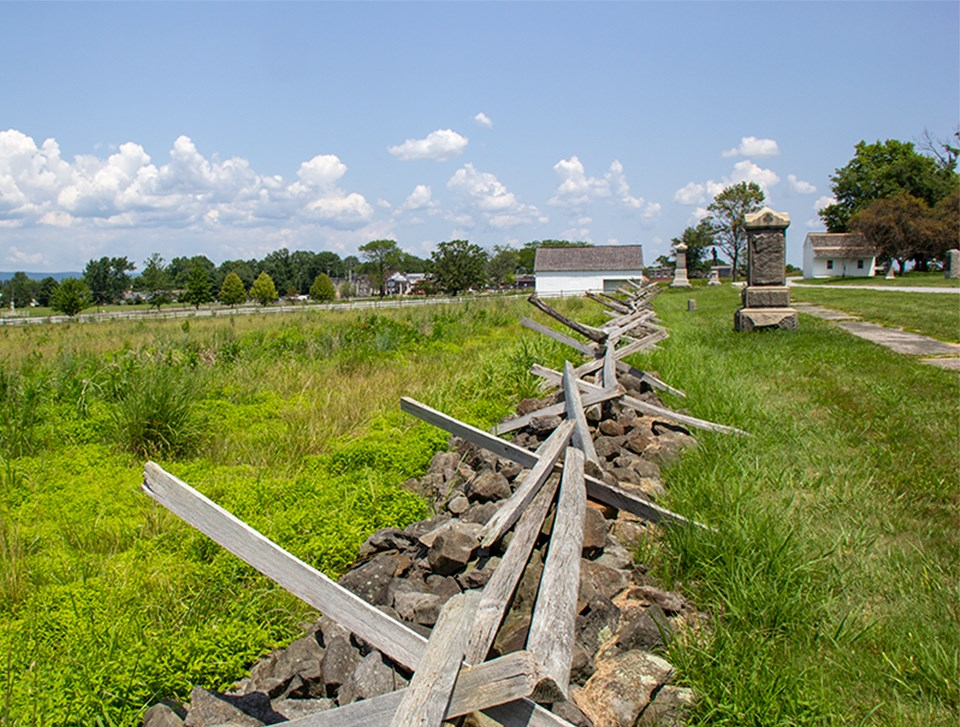 A stone wall with wooden fence toppers run down the center of the picture towards a small white barn. Two small monuments are in the distance on the right.