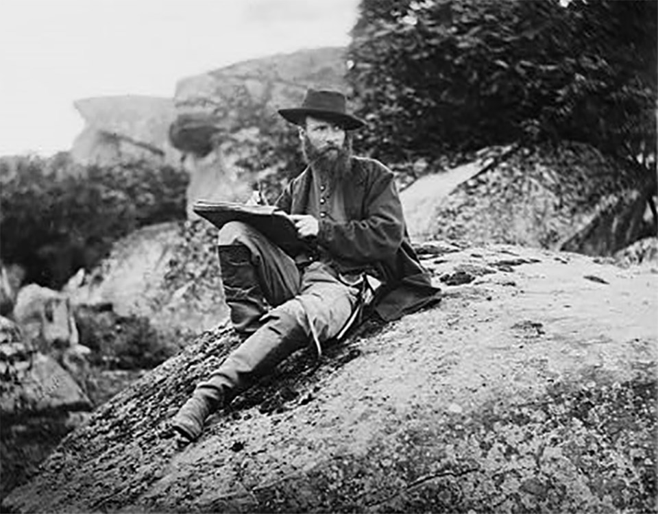 A Civil War sketch artist, Alfred Waud, sits atop a boulder in Devil's Den as he poses for a picture.
