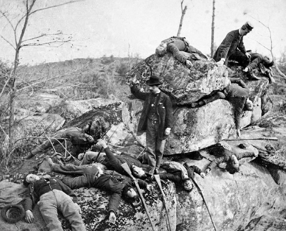 A number of men posing as dead soldiers lie across and underneath rocks in Devil's Den.