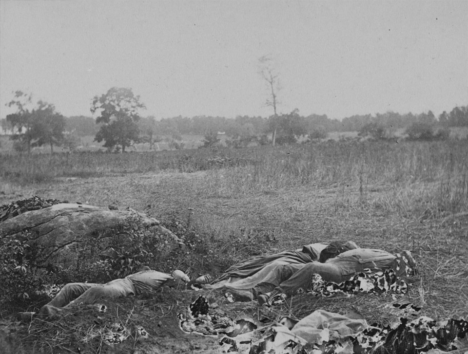 This view looks southwest, away from the Rose Woods. Three dead soldiers lie next to a large rock.