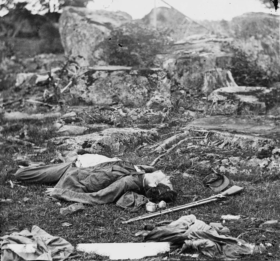 A dead Confederate soldier lies amidst debris in Devil's Den, with a gun and hat near his head.