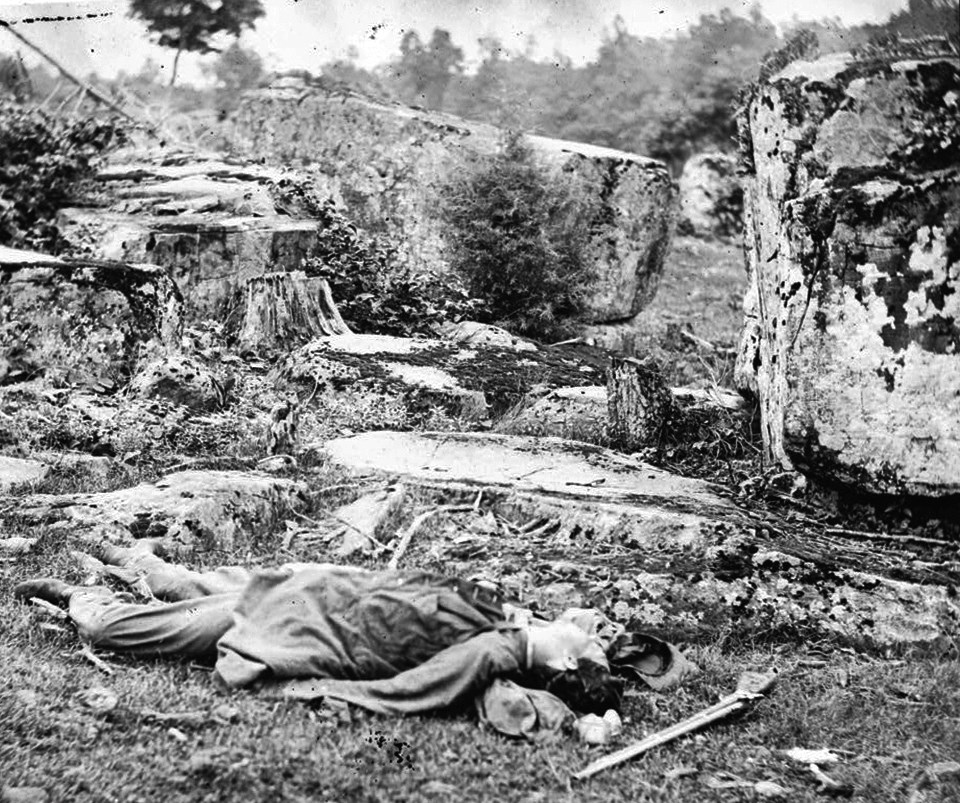 A dead soldier lies in front of rocks in Devil's Den.