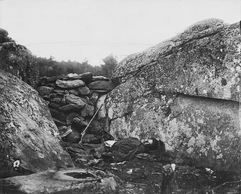 A dead Confederate soldier lies behind a stone fortification, a gun propped against the rocks next to him.