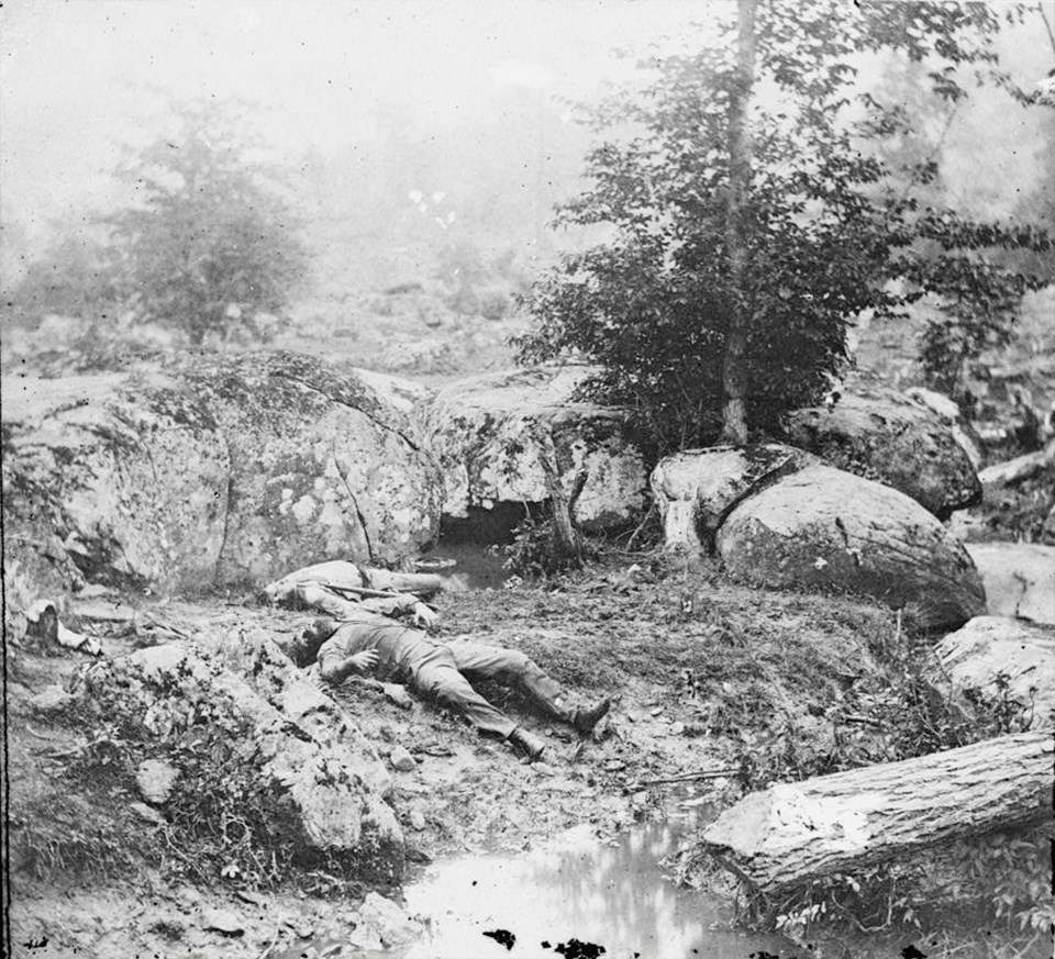 Two dead Confederate soldiers lie on the bank of a small pond, surrounded by large boulders.