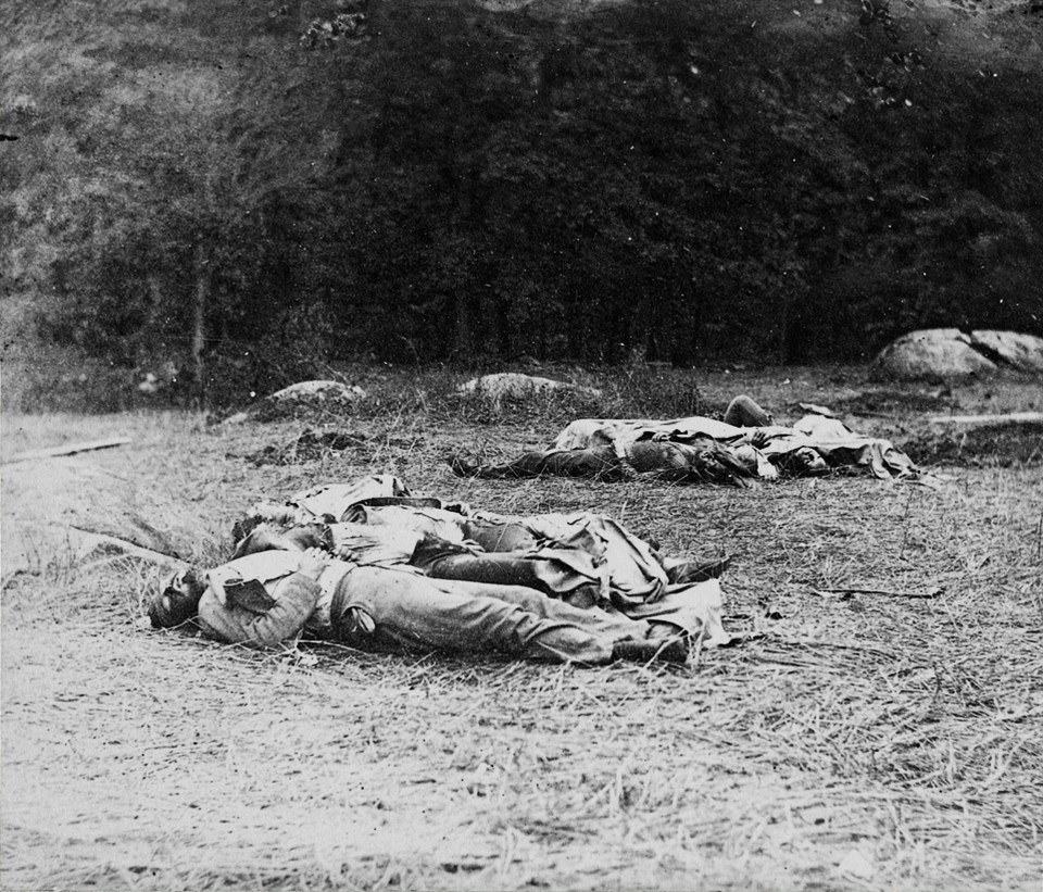 A group of Confederate dead lie near the edge of the Rose Woods.