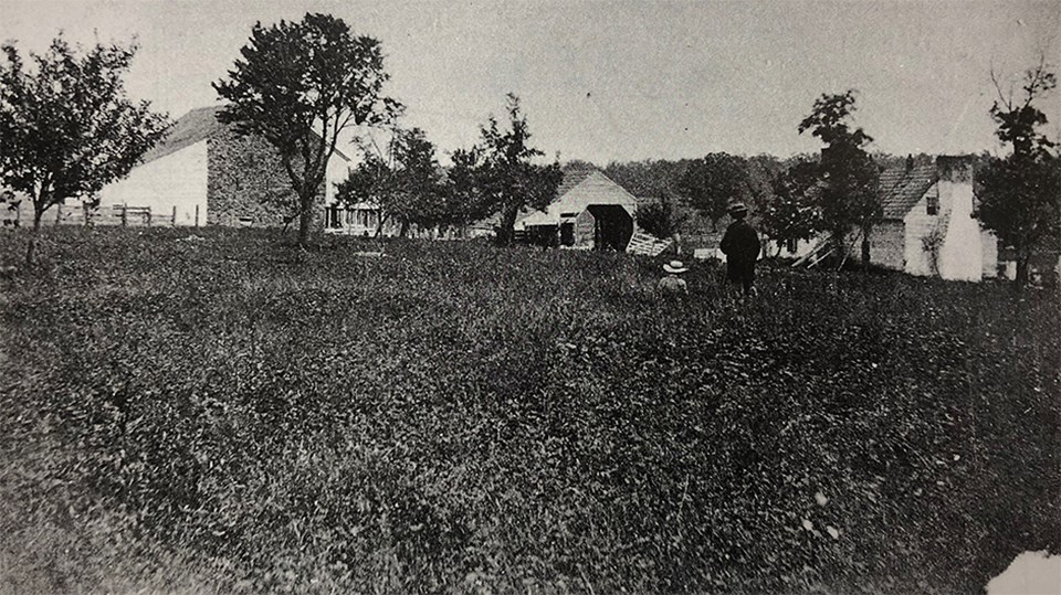 Two men look over a field at a large stone barn, a wagon shed, and a house.