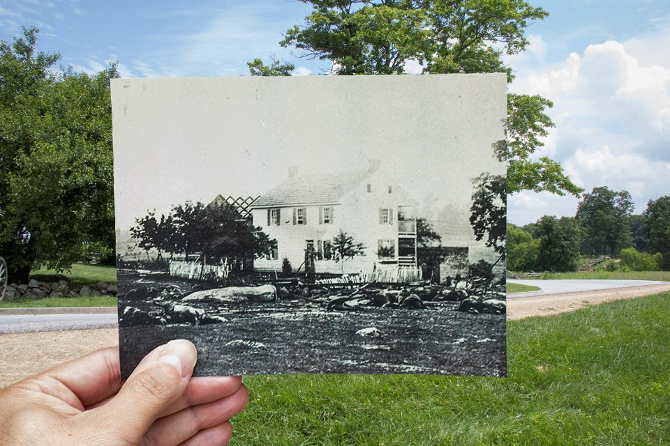 A historic picture of the Trostle house, held up in the center of the modern version, shows numerous dead horses from Bigelow's Battery.