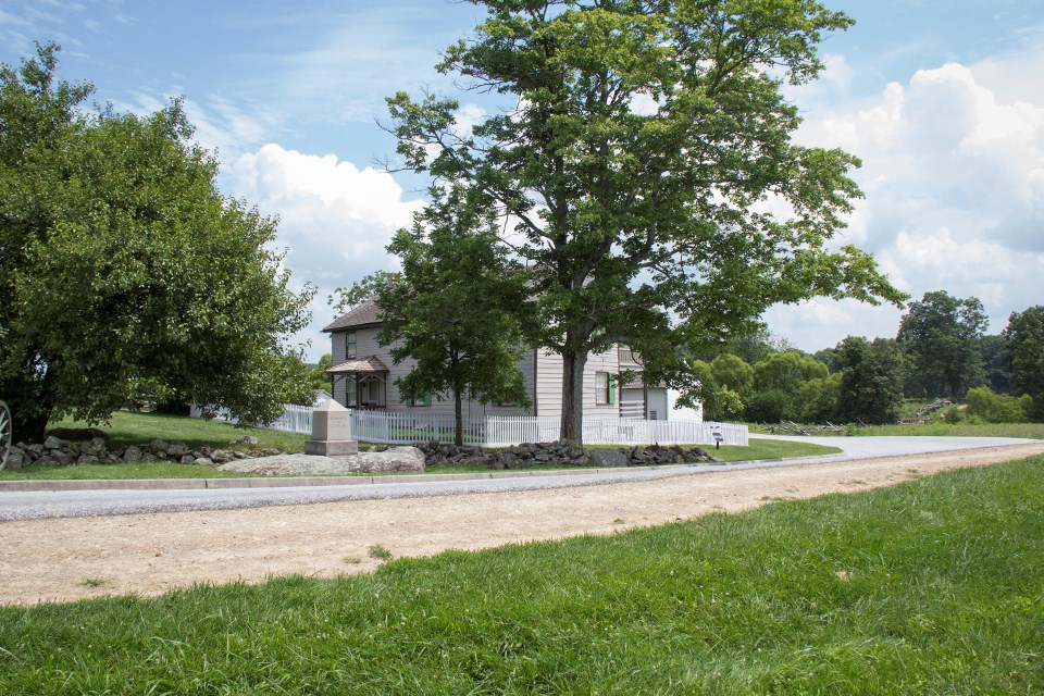 The modern picture of the Trostle house is partially obscured by a large tree. The monument to Bigelow's Battery can be seen on a rock between the house and the road.