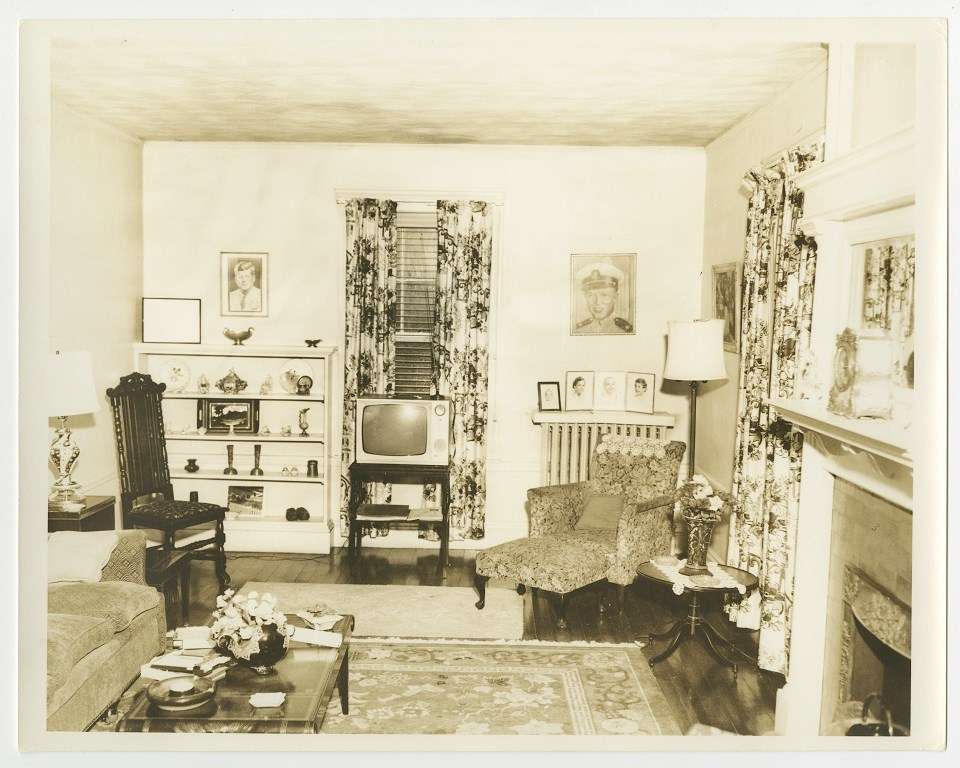Floral curtains hang over two windows in the back of the room.  A TV set sits between the windows.  A gas fireplace is to the right.  A portrait of JFK is on the left back wall.  A chair and couch is to the left.