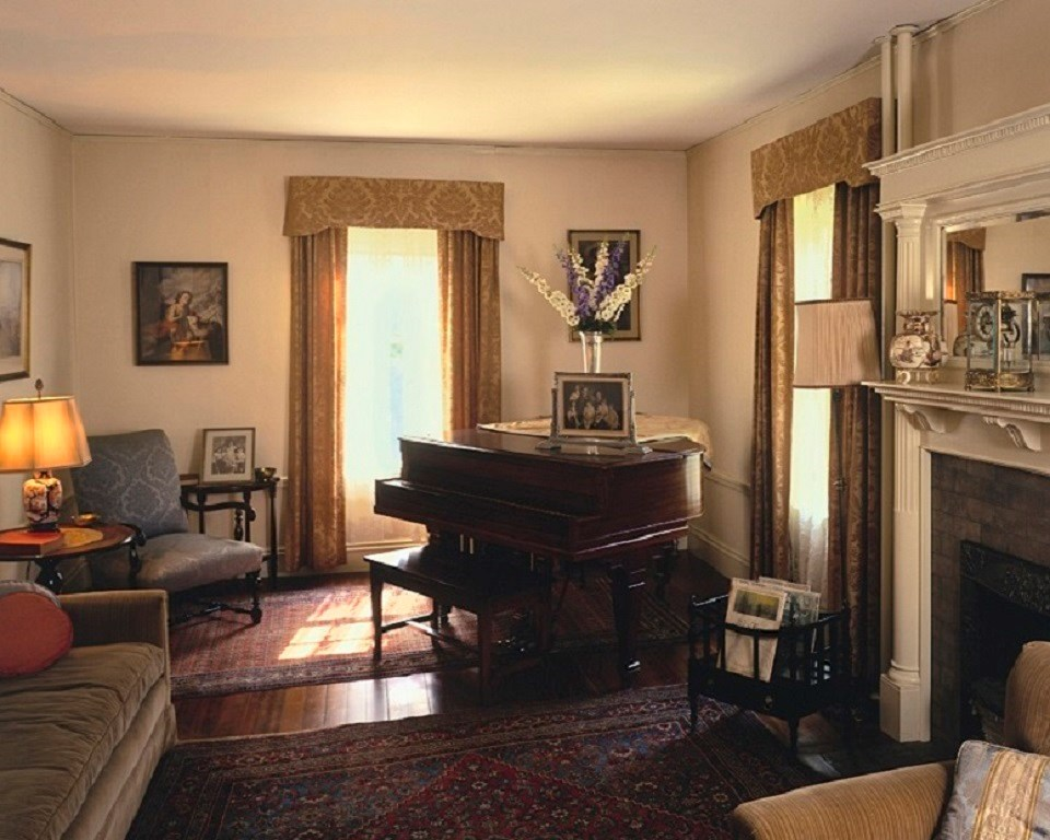 A piano sits in the corner of the room.  A gas fireplace is to the right.  A tan chair is in the right forefront of the photo.  The dark wooden floor is adorned with accent rugs.