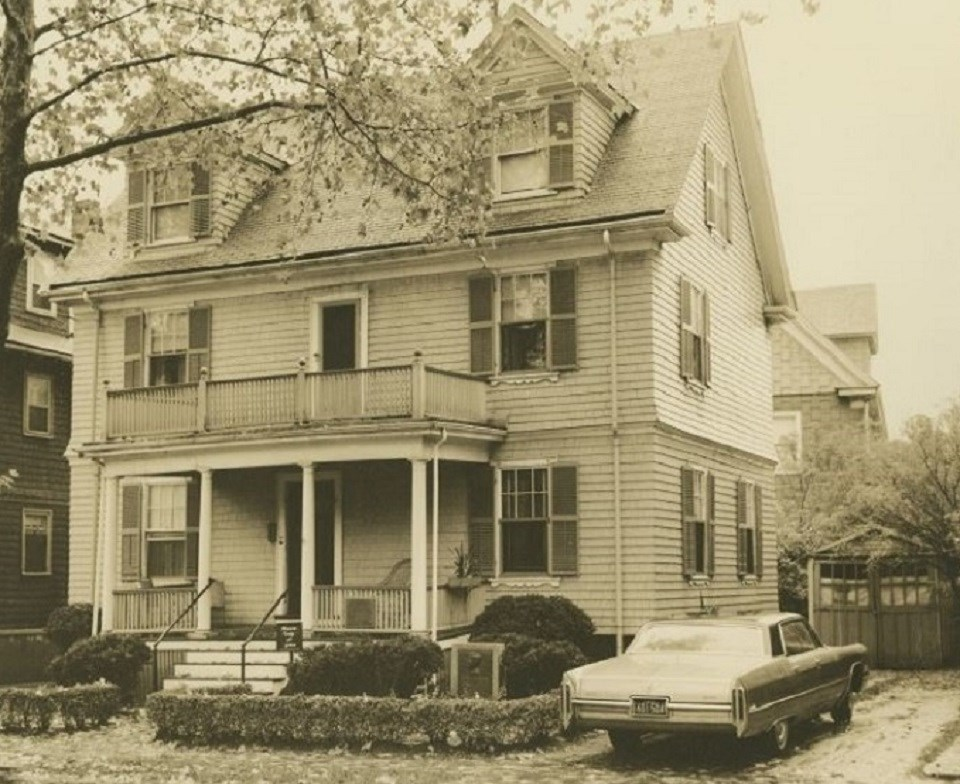 A black and white photo of the JFK Birthplace.  A light colored colonial house with dark shutters.  A tall leafless plane tree stands to the left front of the house.  A car sits on the right of the house.