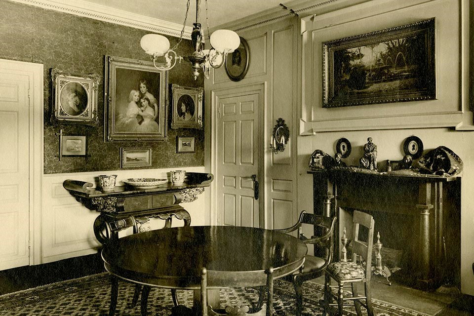 Black and white photograph of room with round table at center, paintings on walls