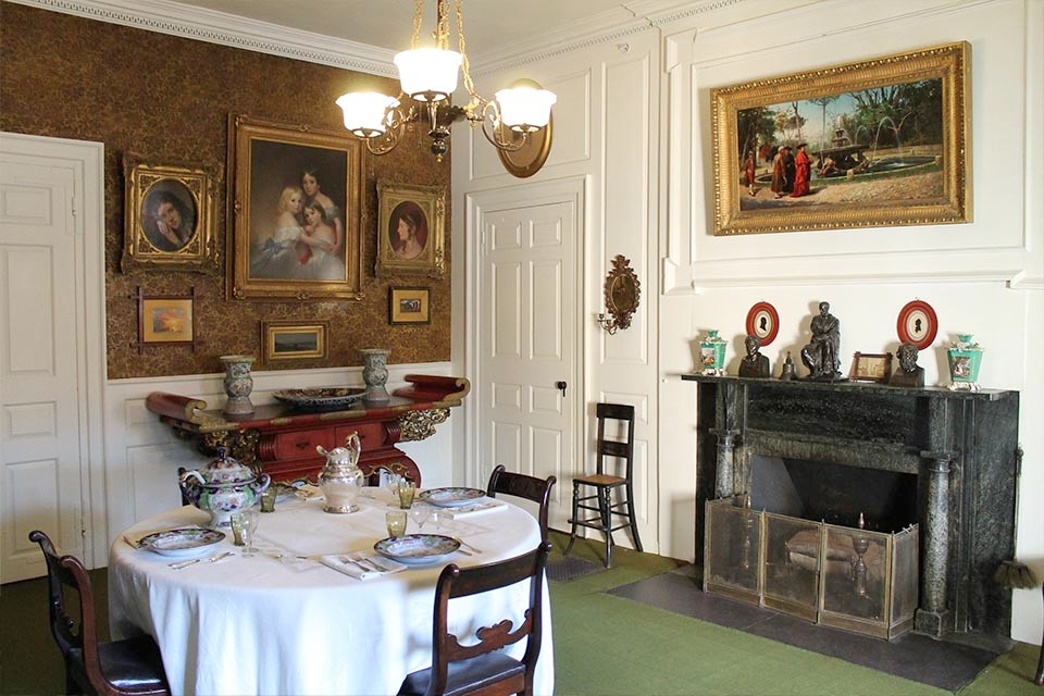 Interior of room with dining table set for four, many paintings hanging on wals