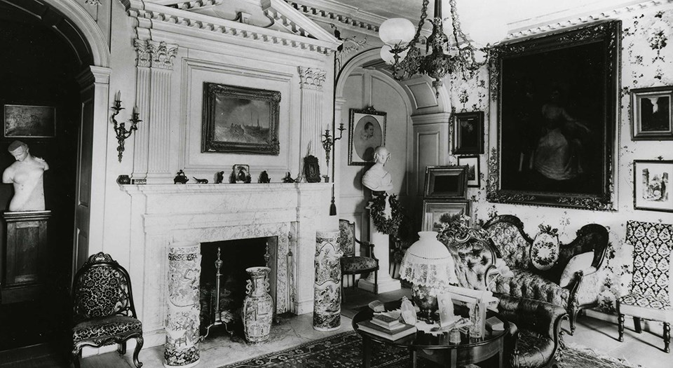 Black and white photograph of room with fireplace, couches and chairs, a gas chandelier, and many paintings on the walls