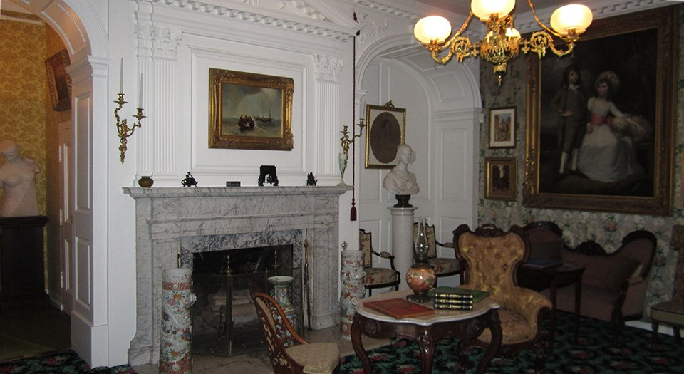 Room with fireplace, couches and chairs, a gas chandelier, and many paintings on the walls