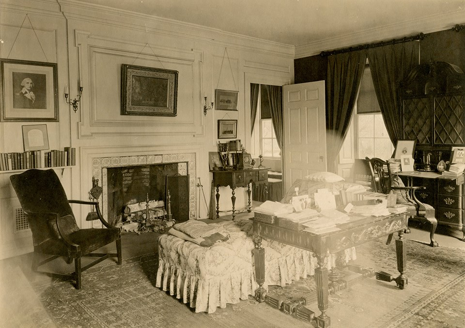 Black and white image of room with table piled with books and chaise at center.
