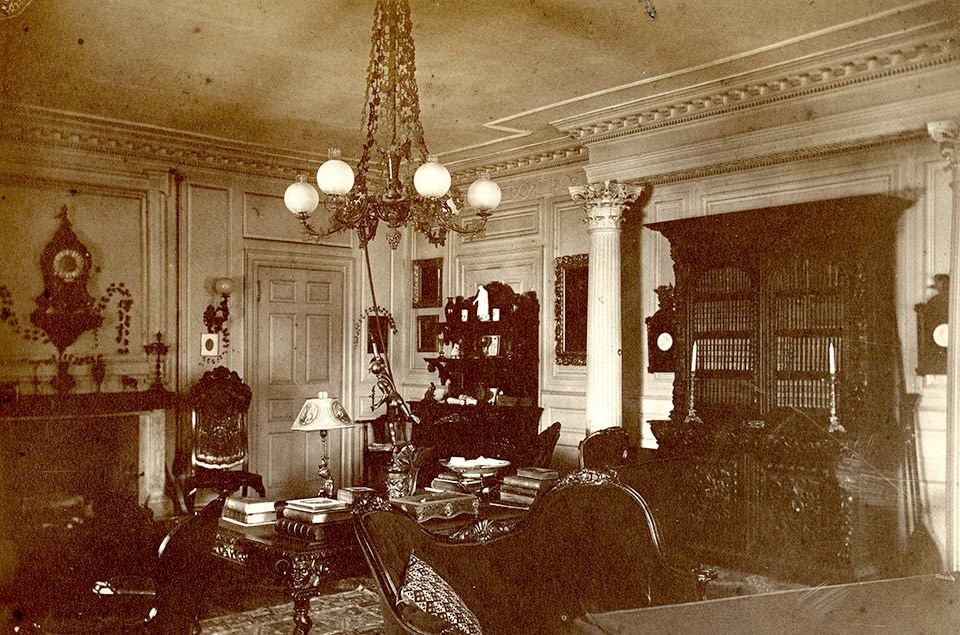 Black and white photograph of Victorian interior with ornate furniture including bookcase and table piled with books.