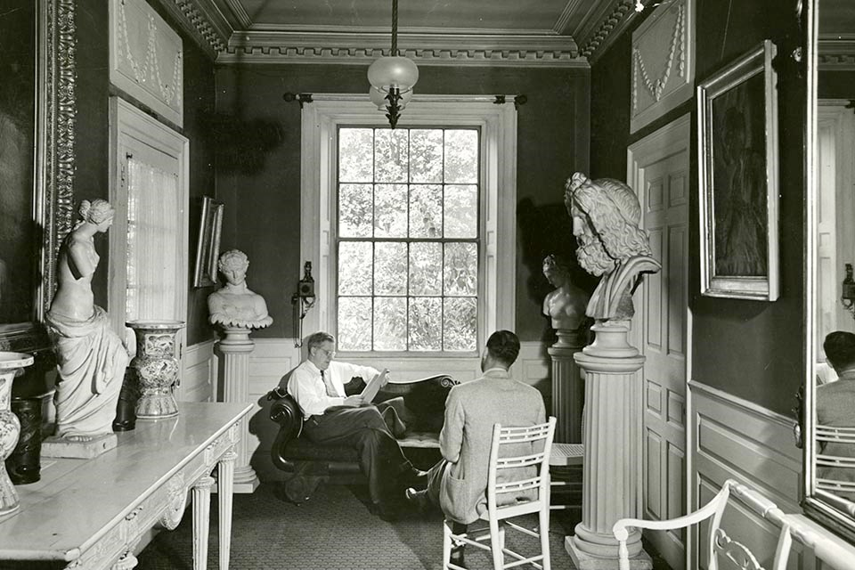 Two men seated in front of a large window, surrounded by statuary.