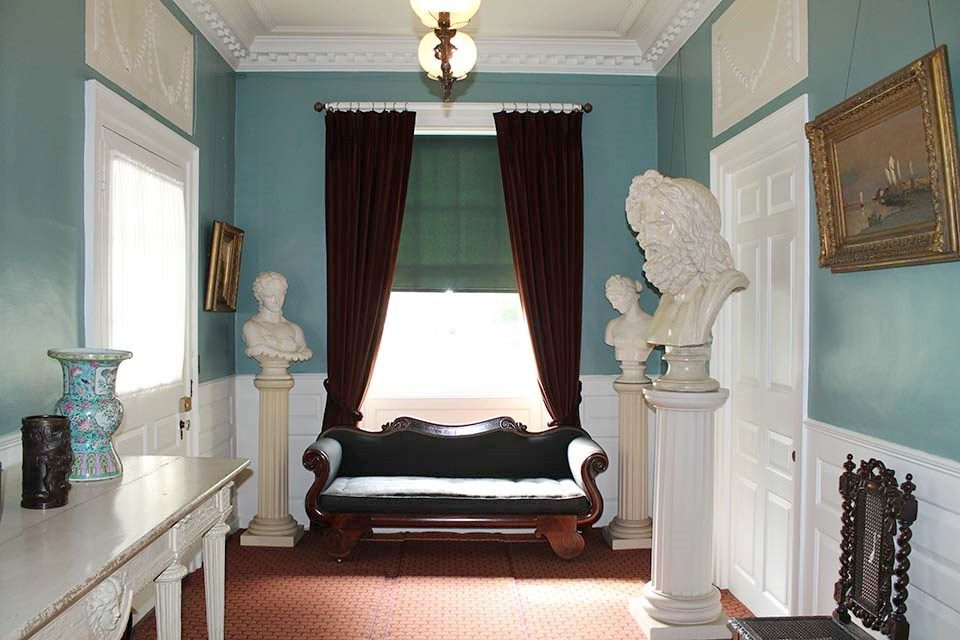Sofa in front of window at end of hall, surrounded by statuary.