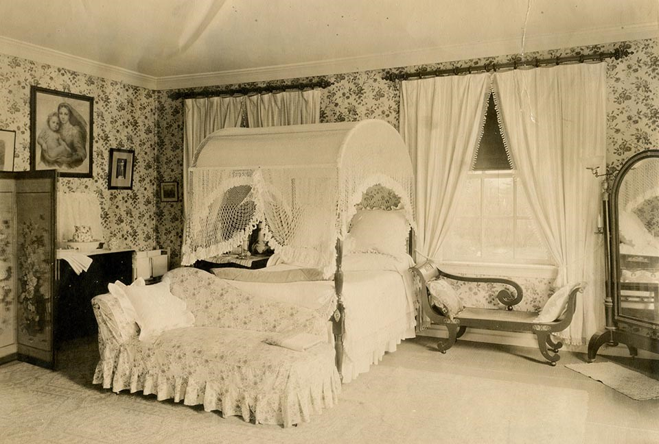 Interior of room with canopy bed and two chaise lounges