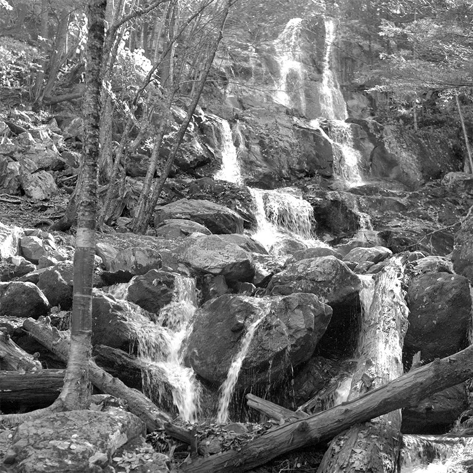 A black and white photograph of a tall waterfall in a forest.