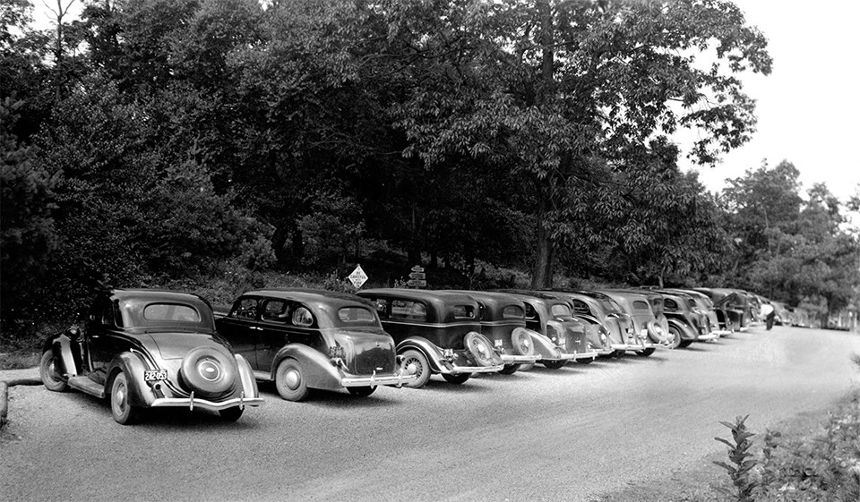 A black and white photograph of a parking lot with cars in it.
