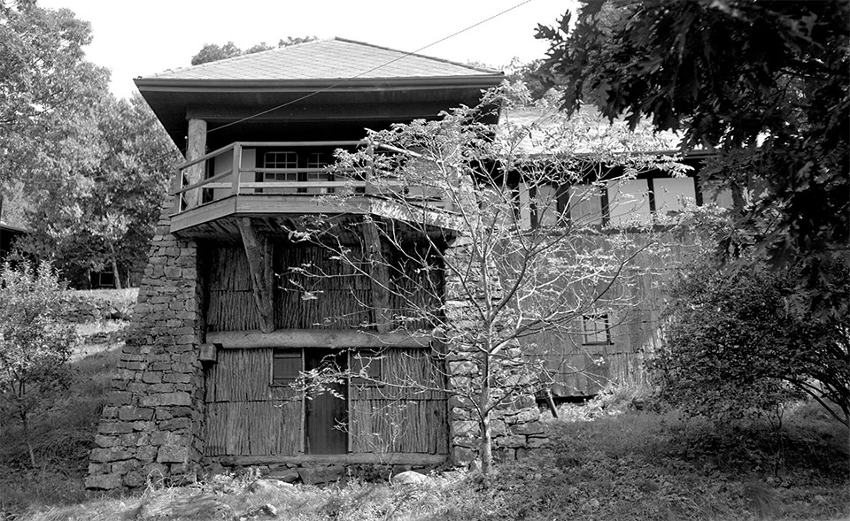 A black and white photograph of a rustic two-story cabin.