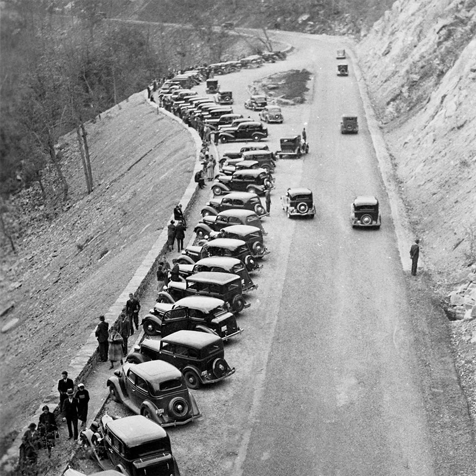 A black and white photograph from above looking down at a long overlook with lots of vehicles.