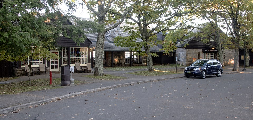 A color photograph of a lodge with a driveway.