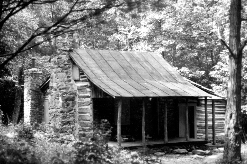 A black and white photograph of a log cabin in the woods.