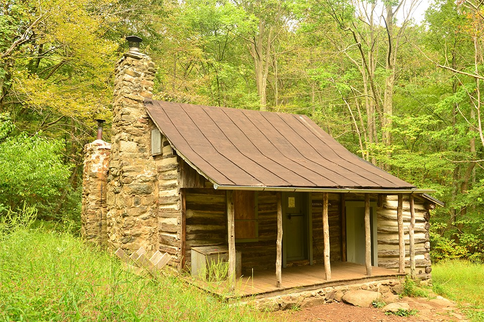 A color photograph of a log cabin in the woods.