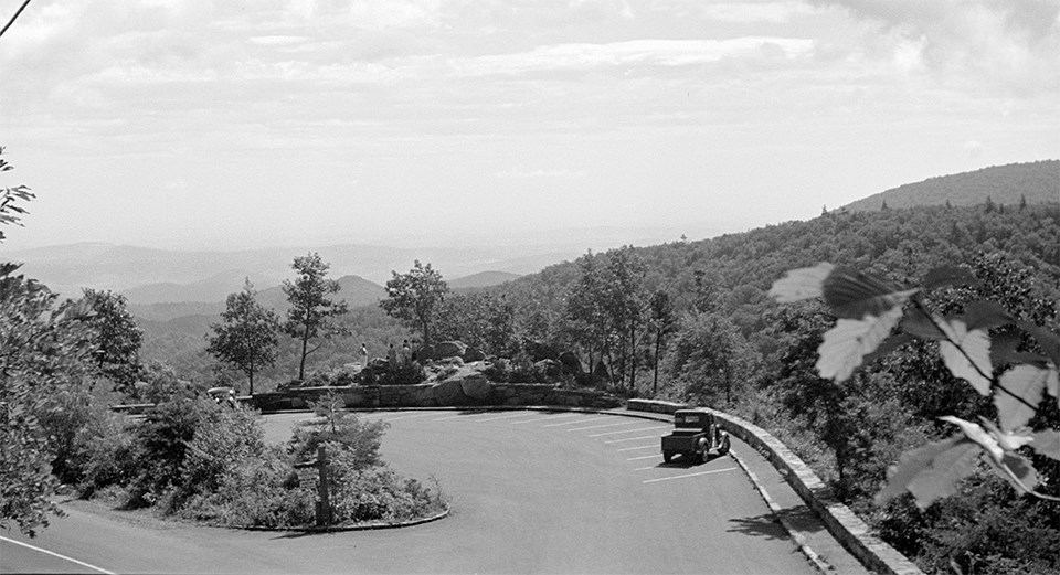 A black and white photograph of an overlook with mountain sin the distance.