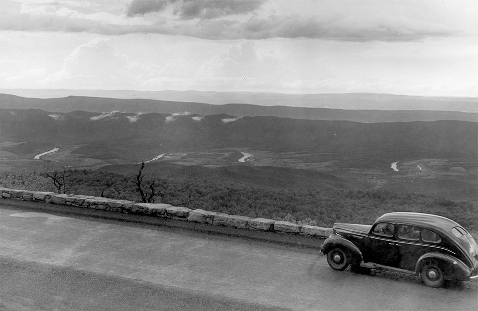 A black and white photograph of an overlook with a vehicle and valley in the distance.