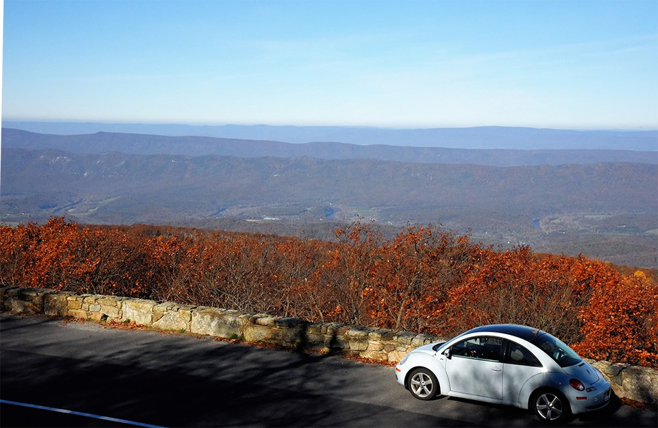 A color photograph of an overlook with a vehicle and valley in the distance.
