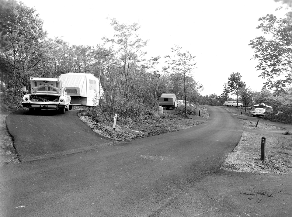 A black and white photograph of a road through a campground.