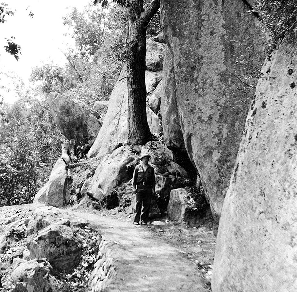 A black and white photograph of a person standing on a trail along a mountainside.