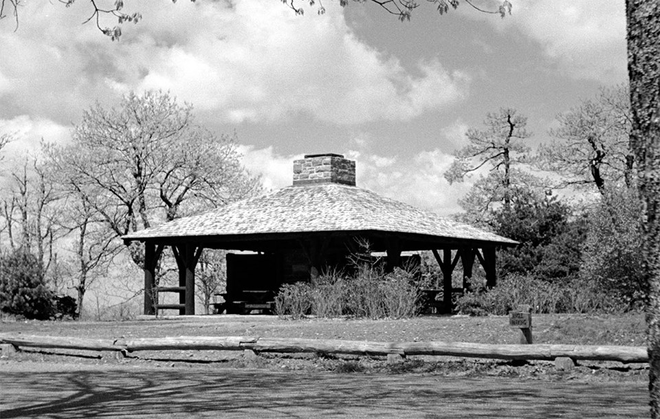 A black and white photograph of a picnic shelter.