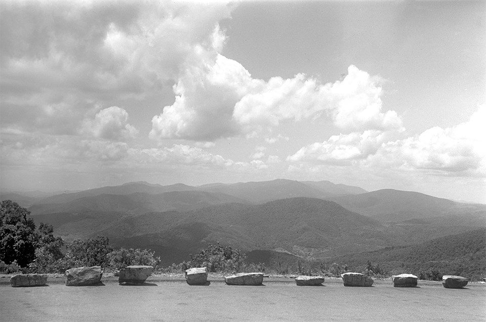 A black and white photograph of an overlook with mountains in the distance.