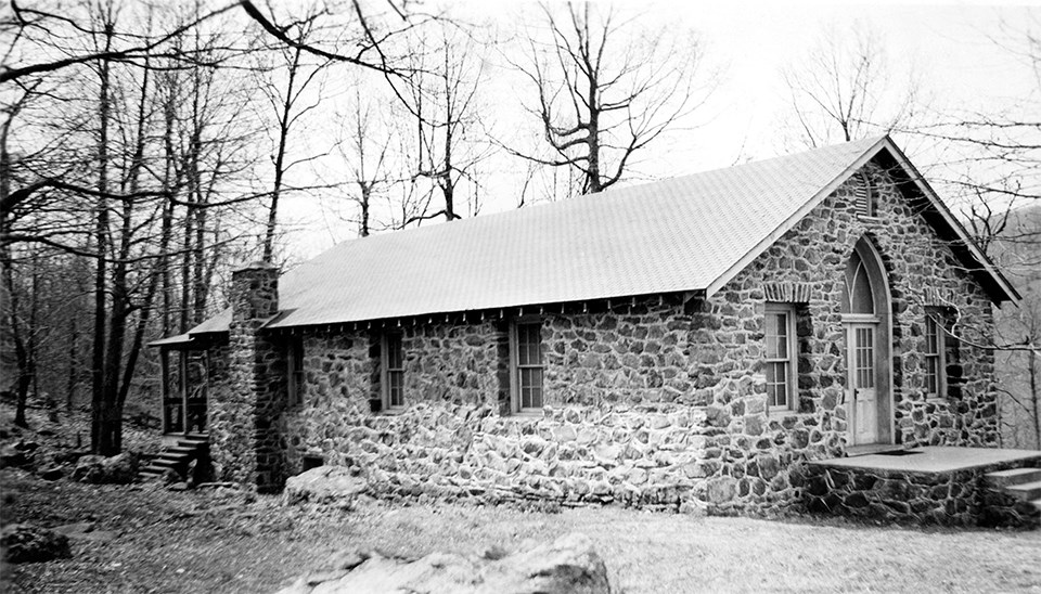 A black and white photograph of a stone building in the woods.