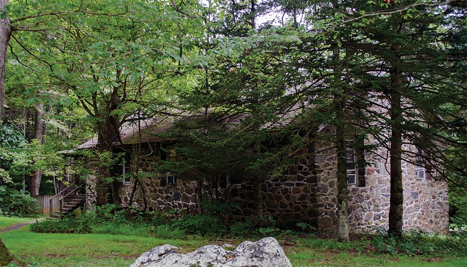 A color photograph of a stone building in the woods.