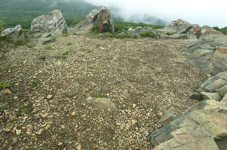 A flat area on a rock outcrop with no vegetation.